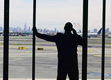 Man speaking on cell phone, while viewing the runway through the waiting area window